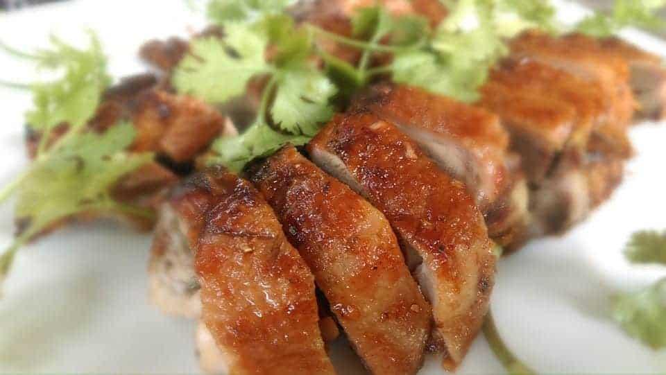 Cayenne roasted quail sliced on a plate.