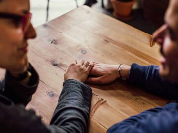 Couple holding hands at a table in coffee shop.