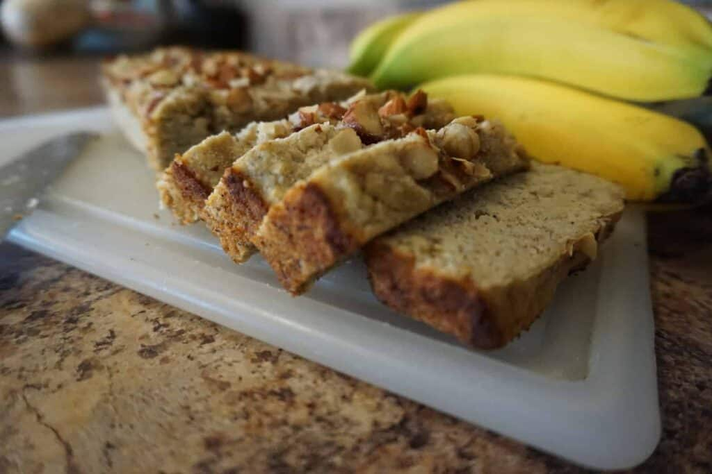 Keto banana bread slices on cutting board next to whole bananas.