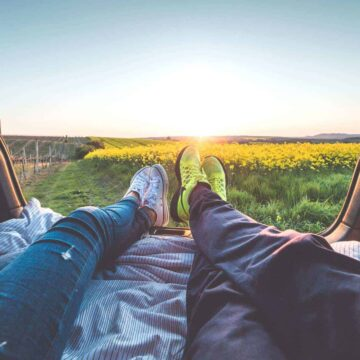 Stress Management Tips: Man and woman relaxing in bed of a truck facing field of yellow flowers and sunset.