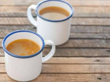 bone broth benefits - two mugs of bone broth on a wooden table