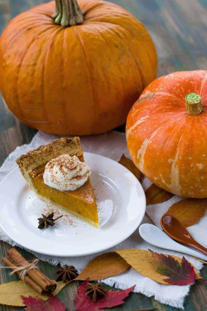 dairy-free keto pumpkin pie with coconut whipped cream and pumpkins on a table
