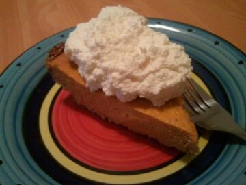 slice of low-carb pumpkin pie with almond crust topped with whipped cream on a plate