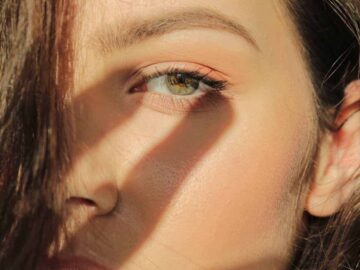 woman shielding her eyes from the sun, shadow of hand on her face - The Power of Antioxidants for Staying Young