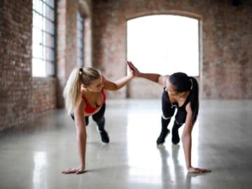 Young women high fiving at the gym - How to Stay Motivated to Exercise