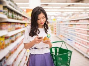 Young woman reading food labels and looking things up on her cell phone