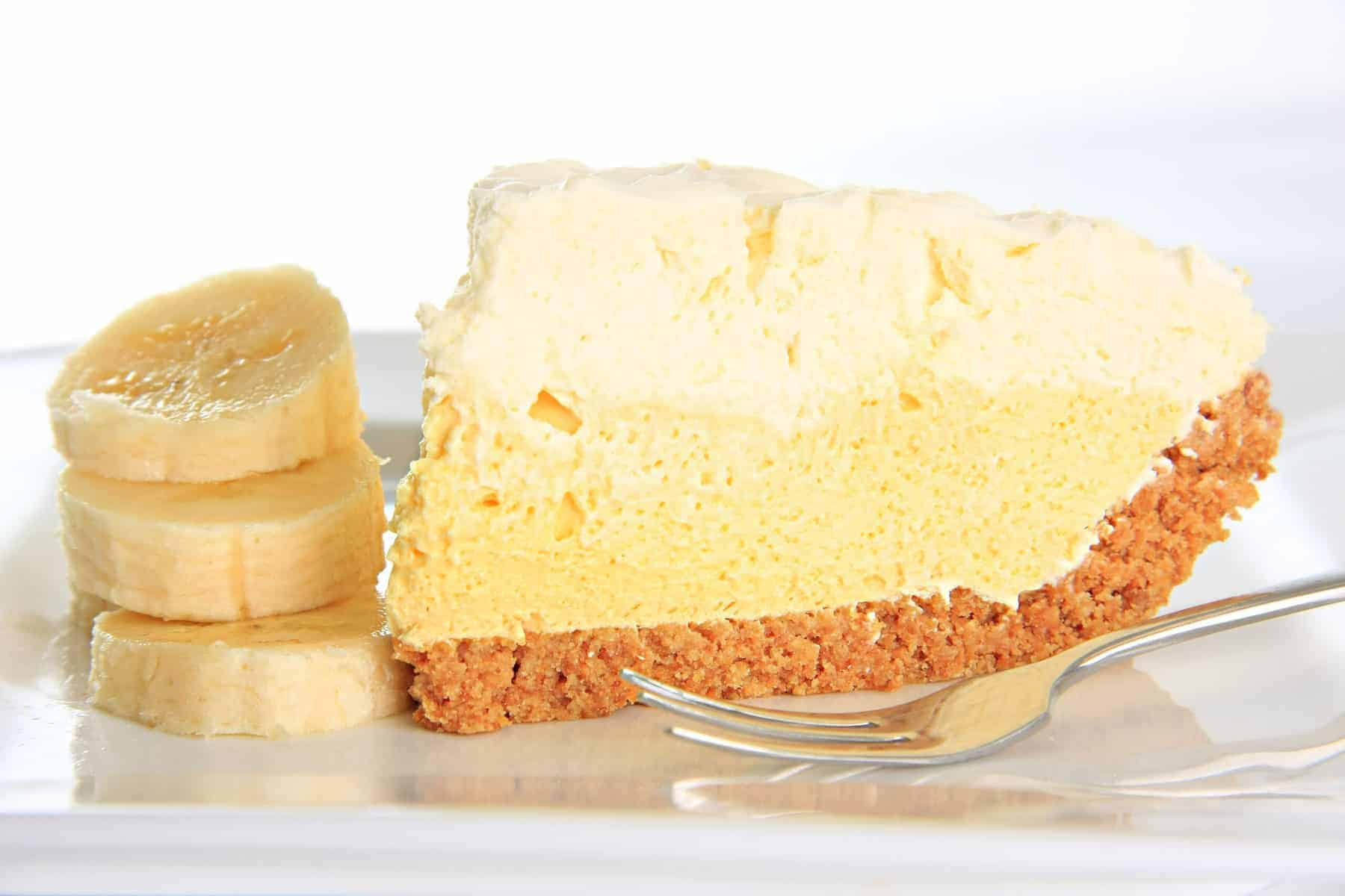 Slice of banana cream pie on a plate with a stack of banana slices