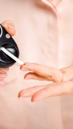 Woman Using a Blood Glucose Ketone Meter