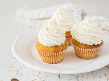 Vanilla cupcakes on white wood background